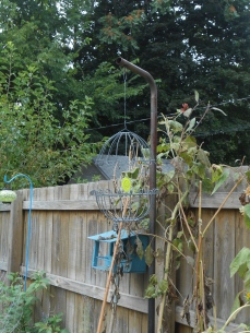 I created a faux birdcage for my flower bed by attaching two planter bases together with wire and hanging a broken glass star in the middle.
